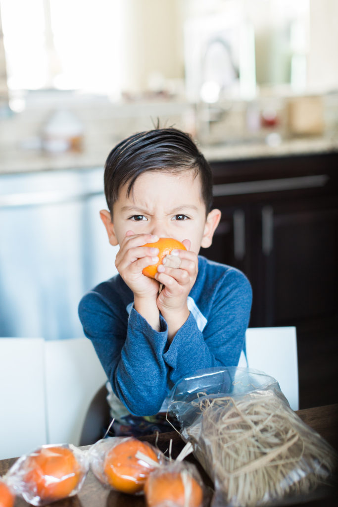 kid biting an orange